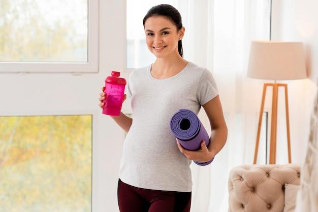 Mulher grávida feliz segurando uma esteira de ginástica e uma garrafa de água