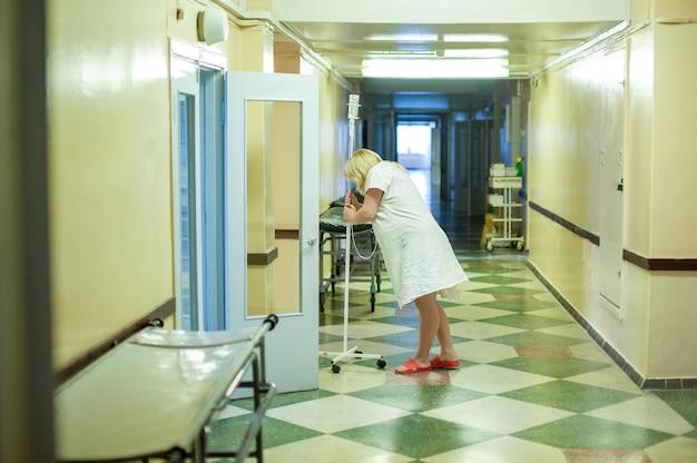 Mulher grávida fica parada no corredor de uma maternidade antes do parto