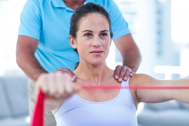 Mulher gravida focalizada que estica a faixa do exercício