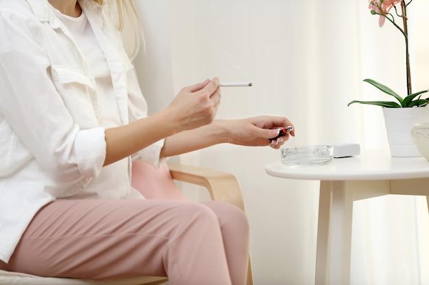 Mulher grávida fumando sentada na cadeira