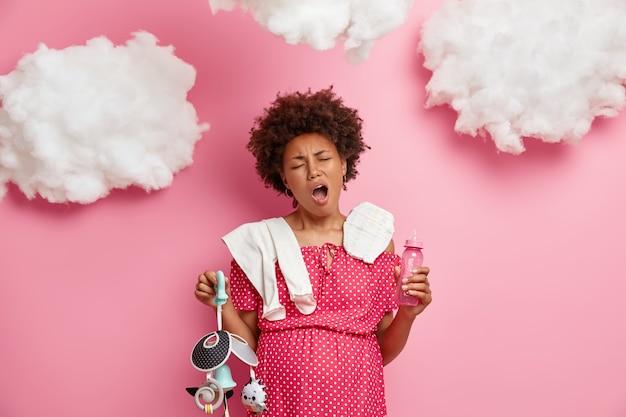 Mulher grávida grávida boceja e se sente cansada, empacota coisas de bebê na maternidade, posa com fralda, mamadeira, celular, fica em pé sobre uma parede rosada. conceito de gravidez e cansaço
