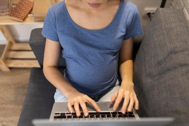Mulher grávida grávida no sofá trabalhando no laptop