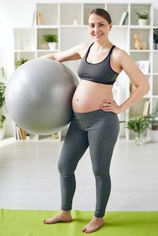 Mulher grávida jovem e positiva com legging cinza e sutiã esportivo em pé com fitball na esteira de ioga em casa
