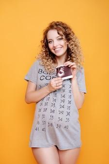 Mulher grávida jovem linda moda loira modelo em estúdio realiza teste de ultrassom em smilles de fundo amarelo laranja