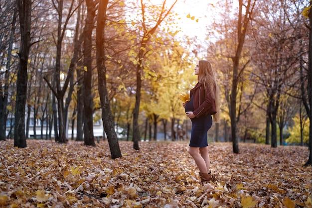 Mulher grávida jovem pensativa. oitavo mês. parque de outono ao fundo