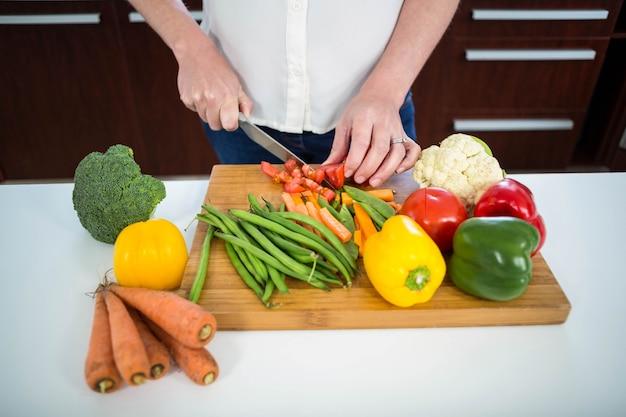 Mulher grávida, legumes cortantes, cozinha