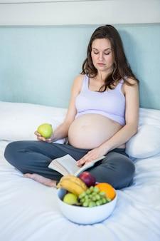 Mulher grávida, lendo um livro, mentindo, ligado, dela, cama