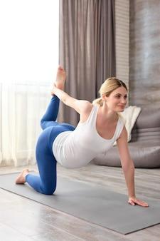 Mulher grávida levanta a perna por trás treinando em casa durante o tempo livre