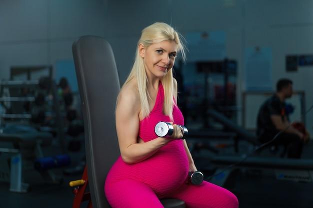 Mulher grávida levantando halteres treinando o músculo bíceps no banco do assento da academia gravidez, estilo de vida saudável, esporte e conceito de fitness treinamento de treino de atleta feminina branca