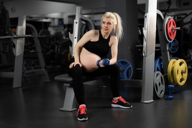 Mulher grávida levantando halteres treinando o músculo bíceps no banco do assento da academia gravidez, estilo de vida saudável, esporte e conceito de fitness treinamento de treino de atleta feminina