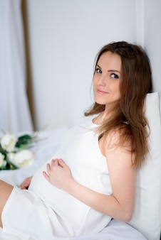 Mulher grávida linda em um vestido branco com um buquê de flores