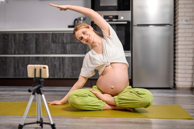 Mulher grávida loira e flexível fazendo exercícios de ioga assistindo vídeo online