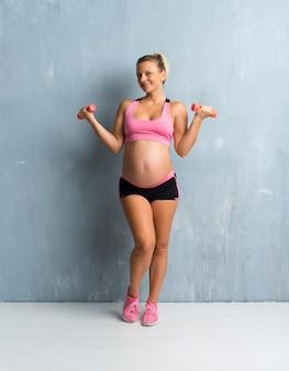 Mulher grávida loira fazendo esporte fazendo halterofilismo