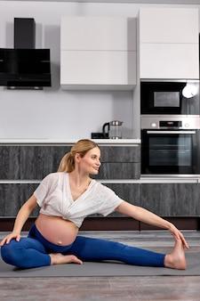 Mulher grávida loira, mãe, grávida, com roupas esportivas, fazendo exercícios no tapete de fitness