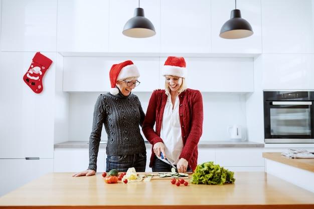 Mulher gravida loura caucasiano de sorriso que prepara a refeição saudável para o jantar de natal. ao lado dela, de pé, a mãe. ambos com chapéus de papai noel na cabeça. interior da cozinha.