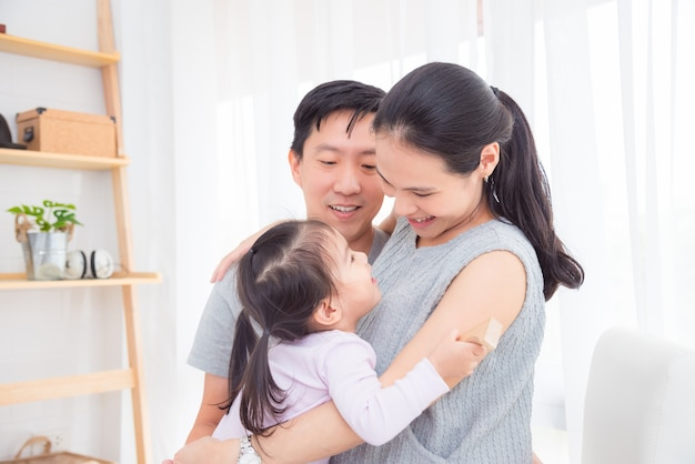 Mulher grávida mãe abraçando sua filha e seu marido em casa