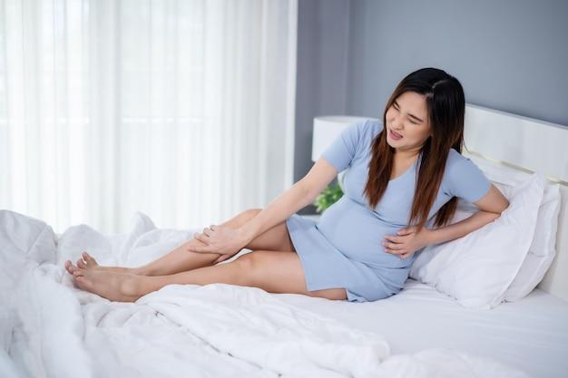 Mulher grávida massageando a perna na cama, músculo dolorido, entorse ou cãibra
