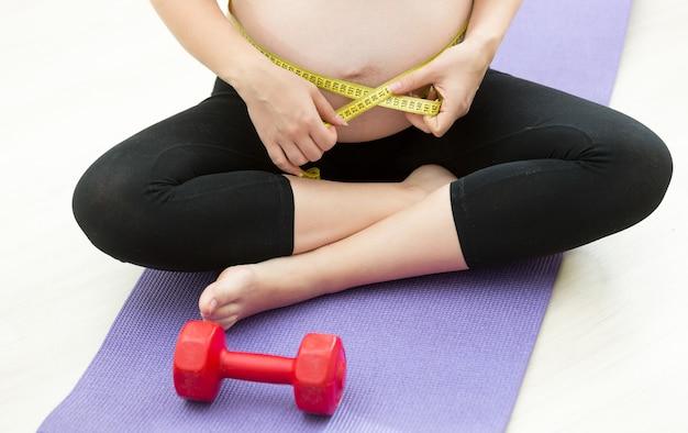 Mulher grávida medindo a barriga com fita adesiva após se exercitar na esteira de ginástica