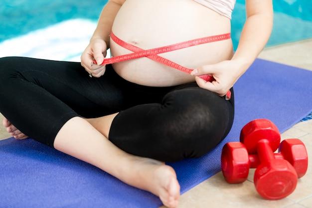 Mulher grávida medindo a barriga no tapete azul de fitness