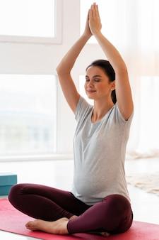 Mulher grávida meditando em casa