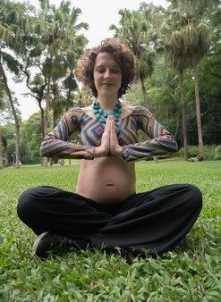 Mulher grávida meditando no parque.
