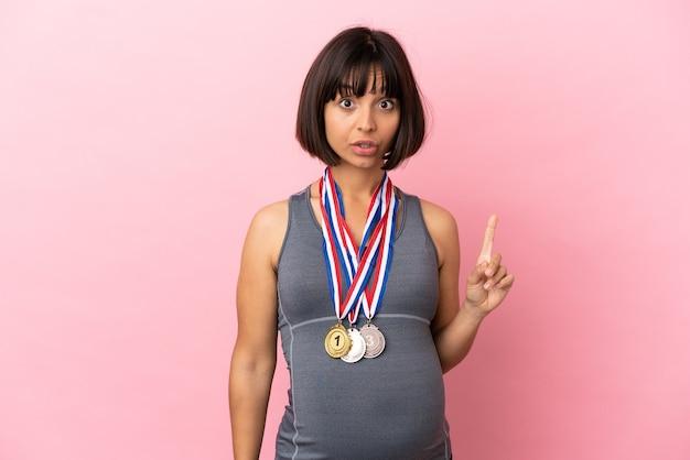 Mulher grávida mestiça com medalhas isoladas em fundo rosa com a intenção de perceber a solução enquanto levanta um dedo