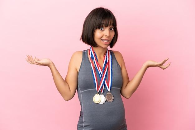 Mulher grávida mestiça com medalhas isoladas em fundo rosa tendo dúvidas ao levantar as mãos