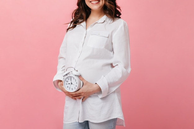 Mulher grávida morena alegre feliz amplamente sorri. senhora encaracolada de camisa branca segura o despertador no fundo rosa.