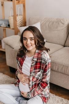 Mulher grávida morena de olhos azuis em uma camisa xadrez e camiseta branca tocando suavemente a barriga e olhando para a frente
