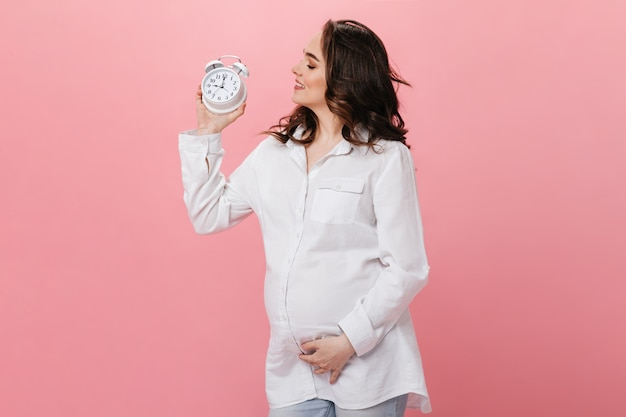 Mulher grávida morena em camisa branca detém despertador isolado. menina charmosa e encaracolada posa em fundo rosa.