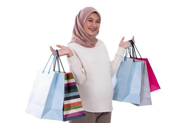 Mulher grávida mostra muitos sacos de compras
