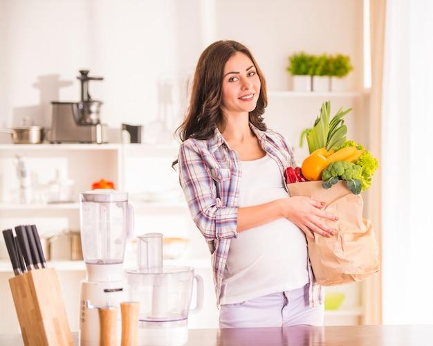 Mulher gravida na cozinha com frutas e legumes.