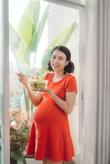 Mulher grávida na sala comendo uma salada sorrindo