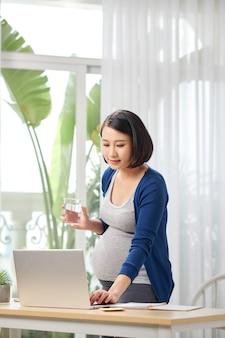 Mulher grávida no escritório em casa perto da mesa com computador e água potável