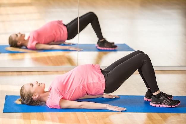 Mulher gravida no exercício da aptidão da ginástica.