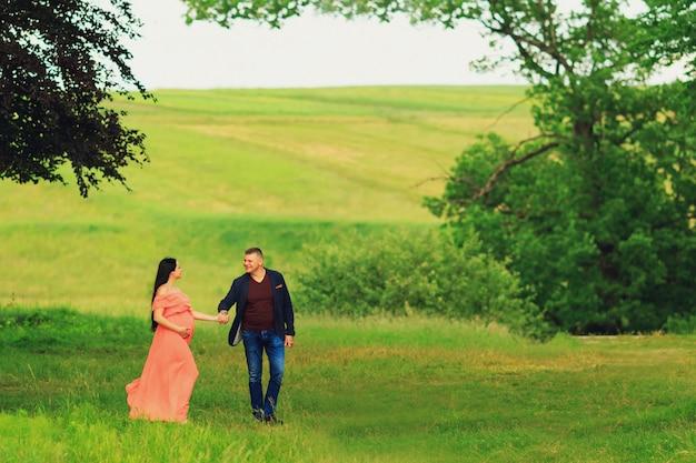 Mulher gravida no vestido alaranjado que anda com seu marido