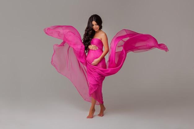 Mulher grávida no vestido de chiffon rosa na luz
