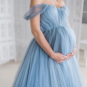 Mulher grávida no vestido rosa mantém as mãos na barriga dela