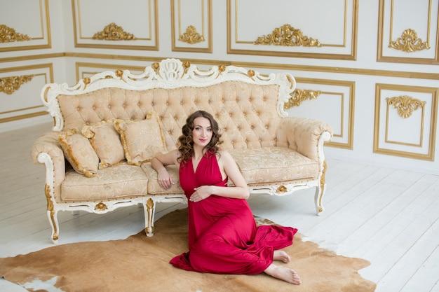 Mulher gravida no vestido vermelho