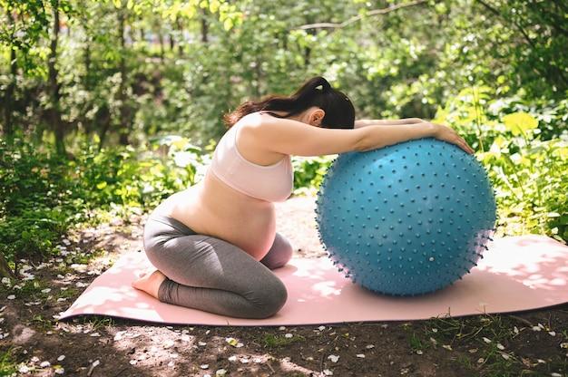 Mulher gravida nova bonita que faz o exercício com a bola azul dos pilates da aptidão no parque ao ar livre