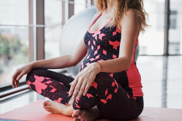 Mulher gravida nova bonita que medita no corredor.