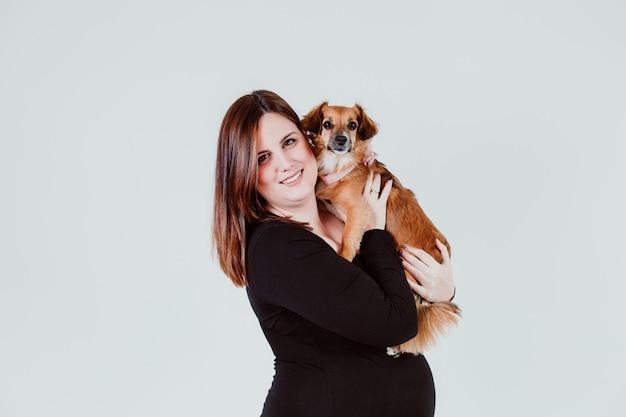 Mulher gravida nova de 21 semanas em casa com seu cão pequeno bonito. conceito de familia