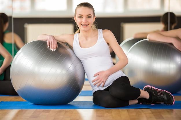 Mulher gravida nova que faz o exercício usando uma bola da aptidão.
