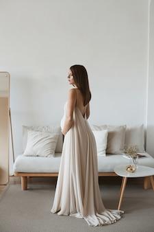 Mulher gravida nova que guarda sua barriga em um interior da sala de visitas. beleza grávida jovem em vestido longo romântico perto do interior do sofá em casa. aguardando bebê.