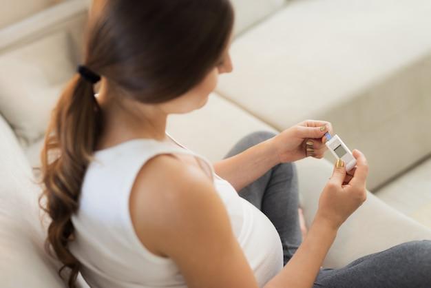 Mulher grávida olha para o dispositivo para medir o açúcar.