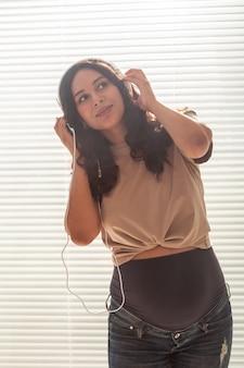 Mulher grávida ouve música em fones de ouvido em casa e dança