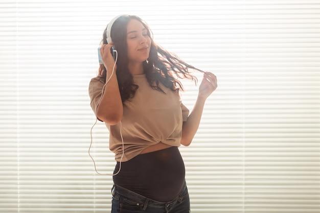 Mulher grávida ouve música em fones de ouvido em casa e danças, copie o espaço.