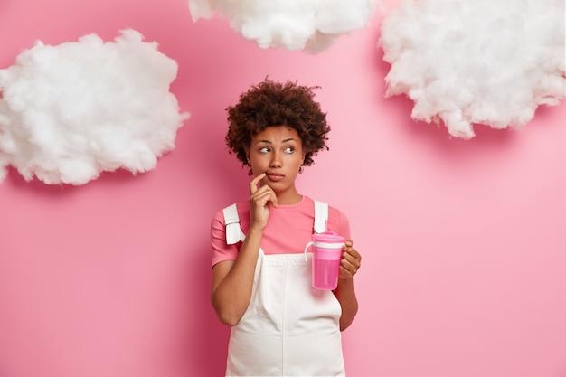 Mulher grávida pensativa olha pensativamente de lado, faz planos sobre o parto, sonha ser mãe, vestida com roupas para futuras mamães, bebe água isolada na parede rosa com nuvens brancas