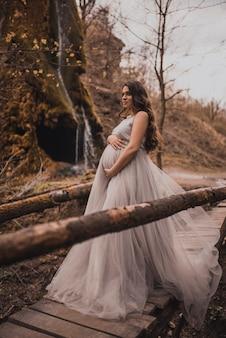 Mulher grávida perto de montanhas caminha ao longo de um