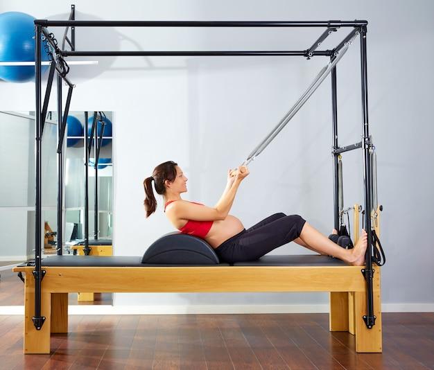 Mulher grávida pilates reformer arregaçar o exercício